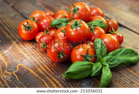 Cherry tomatoes and basil on wooden background - stock photo