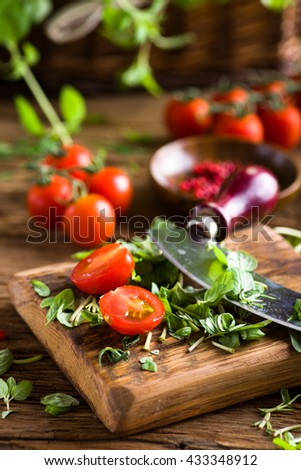 Cherry tomatoes and herbs on old wooden table, shallow dof - stock photo