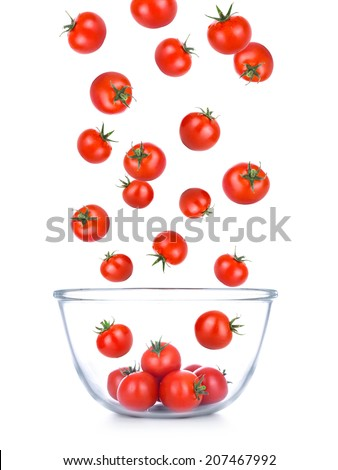 Cherry tomatoes falling into glass bowl, isolated - stock photo