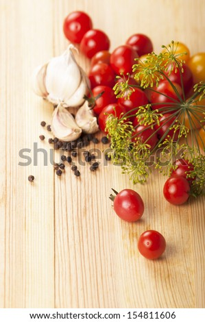 cherry tomatoes, garlic, spices, a fennel branch on a kitchen board - stock photo