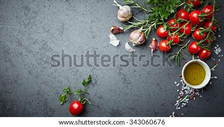 Cherry tomatoes, herbs, spices and olive oil on a stone background - stock photo