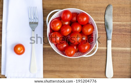 Cherry tomatoes in a white colander with a fork and a knife