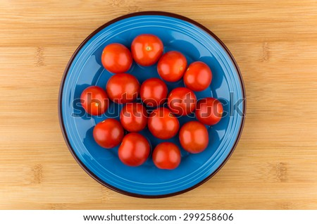 Cherry tomatoes in blue glass plate on wooden table, top view - stock photo