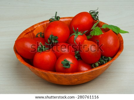 Cherry tomatoes in the basket with fresh green leaf - stock photo