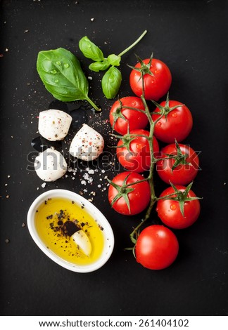 Cherry tomatoes, mozzarella cheese, basil and olive oil on black chalkboard from above. Italian caprese salad recipe ingredients. - stock photo
