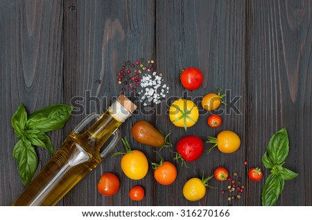 Cherry tomatoes of various color, basil leaves, spices and olive oil from above over dark wooden table. Italian caprese salad recipe ingredients. Top view, free text copy space - stock photo