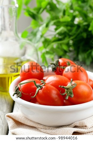cherry tomatoes, olive oil and parsley on wooden background
