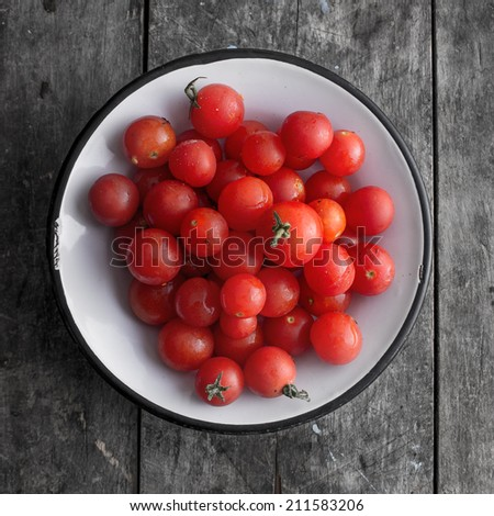 cherry tomatoes on a plate over wooden background, from above - stock photo