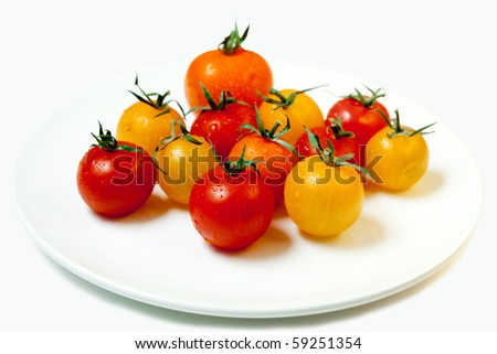 cherry tomatoes on a white plate, isolated on white - stock photo