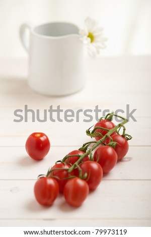 Cherry tomatoes on a white table, white flower in background - stock photo