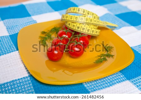 cherry tomatoes on a yellow plate with a flexible measuring tape