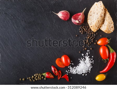 cherry tomatoes on slate with sliced bread, black and green pepper, salt. Place to inscription - stock photo