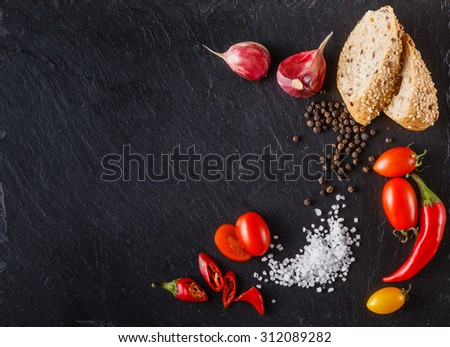 cherry tomatoes on slate with sliced bread, black pepper and salt. Place to inscription - stock photo