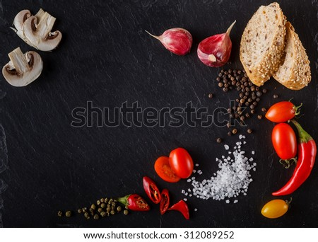 cherry tomatoes on slate with sliced bread, mushrooms, pepper and salt. Place to inscription - stock photo