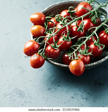 Cherry tomatoes on the vine in a ceramic bowl  - stock photo