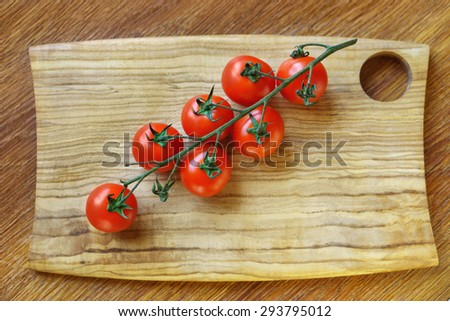 Cherry tomatoes on wood desk - stock photo