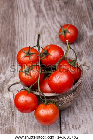 Cherry tomatoes on wooden table with water drops - stock photo