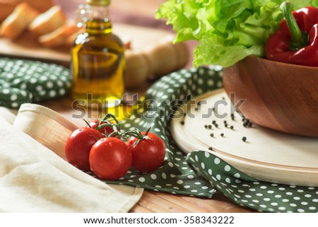 Cherry tomatoes, pepper, salad, sliced bread and a bottle of olive oil on a kitchen table - stock photo