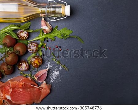 Cherry tomatoes, prosciutto, arugula and spices on black board, top view - stock photo