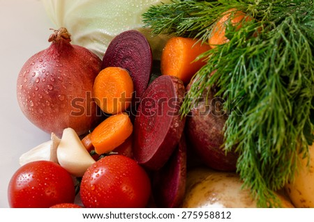 Cherry tomatoes, sliced rings of carrots and beets, potatoes, garlic, onion, dill. Vegetables. Close-up. Horizontal shot. - stock photo