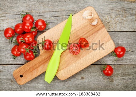 Cherry tomatoes with knife on cutting board over wooden table background - stock photo