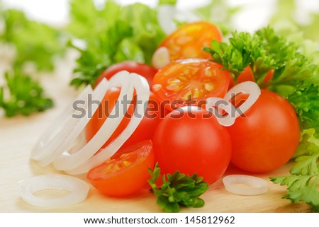 Cherry tomatoes with onion and lettuce on wooden board