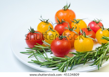 cherry tomatoes with rosemary on a white plate - stock photo