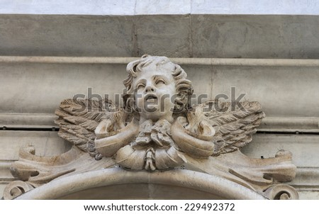 cherub ancient sculpture on the wall of Pisa building
