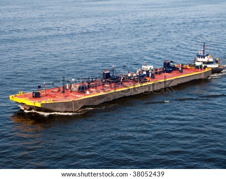 Chesapeake Bay barge guided by a tugboat - stock photo