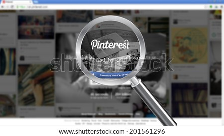 CHESHIRE - JUNE 29, 2014: Photo of Pinterest homepage on a monitor screen through a magnifying glass. - stock photo