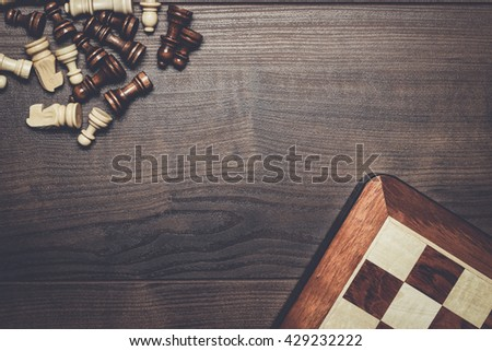 chess board and figures on woden background - stock photo