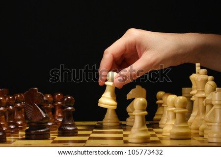 Chess board with chess pieces isolated on black - stock photo