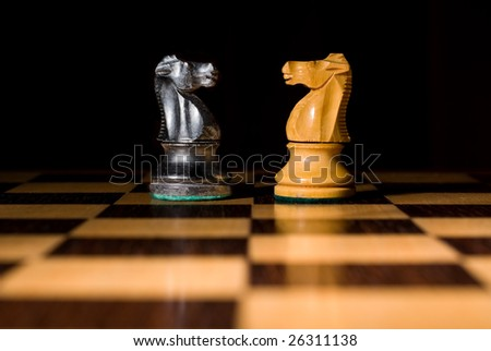 Chess board with 2 knights as example of game or business concept for power, strategy or success - stock photo