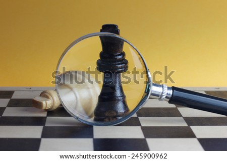 Chess fight concept with two chess kings and magnifying glass, yellow background. - stock photo