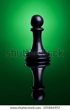 Chess figure - Black pawn  - on a green background - stock photo