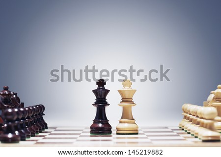 Chess game two kings in centre of board other pieces lined up - stock photo