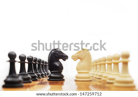 Chess horses facing each other for a standoff - stock photo