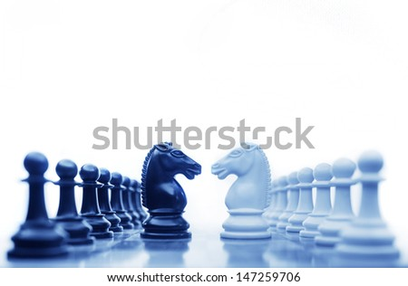 Chess horses facing each other for a standoff in cool tones - stock photo