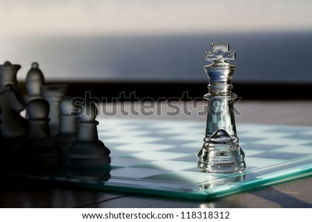 Chess King / Pieces - business concept series - advertising, marketing, sales, strategy, business leadership, mentor, business consultancy - business card. King in light, other chess pieces in shadow. - stock photo