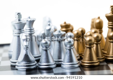 Chess of two colours standing on a board. Small depth of sharpness - stock photo