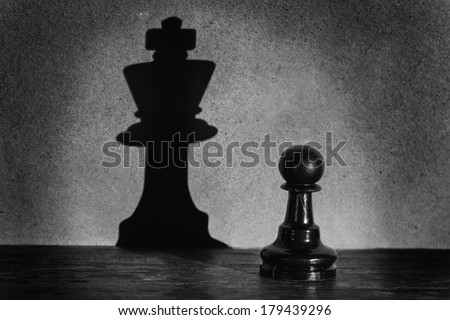 Chess pawn standing in a spotlight that make a shadow of king with darkness artistic conversion - stock photo