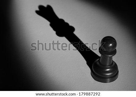 Chess pawn standing in a spotlight that make a shadow of queen with darkness artistic conversion - stock photo
