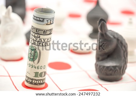 Chess piece with us dollars money or cash, symbol of wealth, business and planning - stock photo