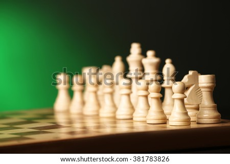 Chess pieces and game board on green background