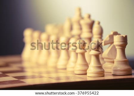 Chess pieces and game board on grey blurred background - stock photo