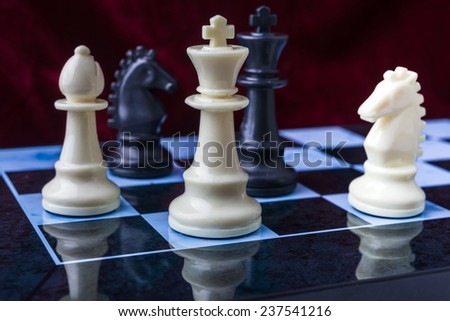 chess pieces. Black and white chess pieces on blue board - stock photo