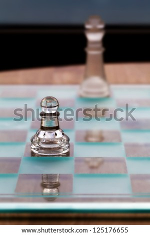 Chess pieces - business concept series: mentoring concept, consultant,  strategy, mentor - help / advice - small pawn up front, king in the background.