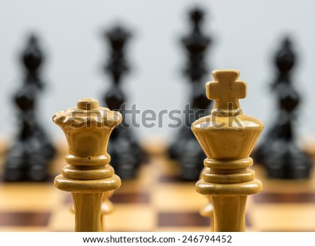 Chess pieces on a chess board. The white king and queen are visible together on the foreground - stock photo