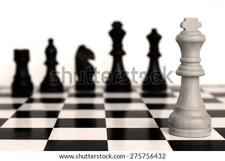 Chess pieces on a chessboard on a light background. - stock photo