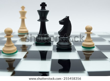 Chess pieces on a reflecting surface - stock photo